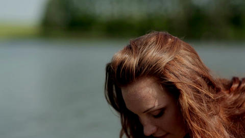 Red-haired girl straightens her hair/ red-haired girl on the bank of the river Archivo