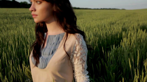 Beauty romantic girl walking alone through the green wheat field and touching Live Action