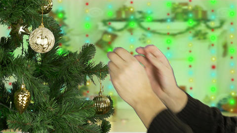 Mans hand decorate christmas tree. Golden lights background. Yellow sphere ball Footage