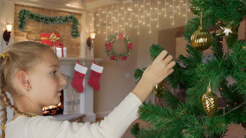 Excited young white girl decorating christmas tree and with happy looking to fir Footage