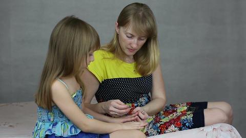 Mom put on nail polish on daughters nails ビデオ