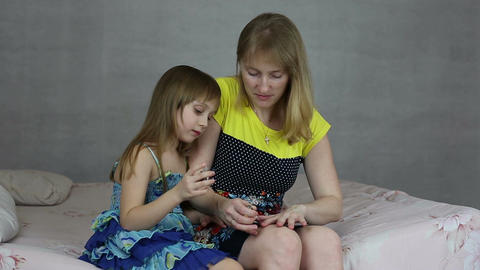 The girl helps her mother to paint her nails nail polish Footage
