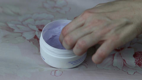 The girl finger takes cream from the jar Live Action