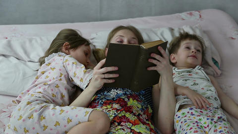 Mom reading the book to son and daughter bedtime Footage