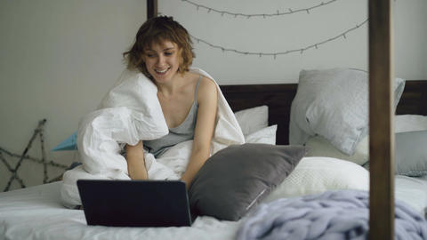 Cheerful young woman using her laptop computer sitting in bed at home Footage