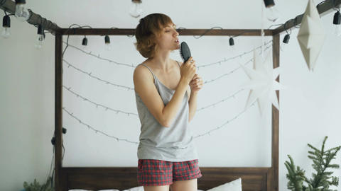 Attractive cheerful woman dancing on bed and singing with comb like microphone Footage