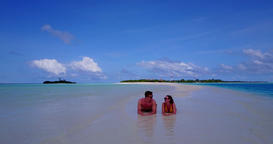 v14823 two 2 people laying romantic young couple sunbathing on a tropical island Archivo