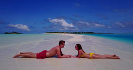 v14838 two 2 people laying romantic young couple sunbathing on a tropical island Footage