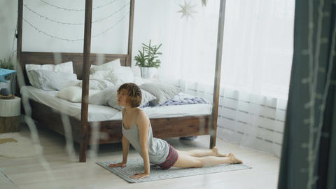 Happy attractive woman doing yoga exercise near bed in bedroom at home Footage