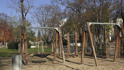 Children playground activities in public park surrounded by trees Image