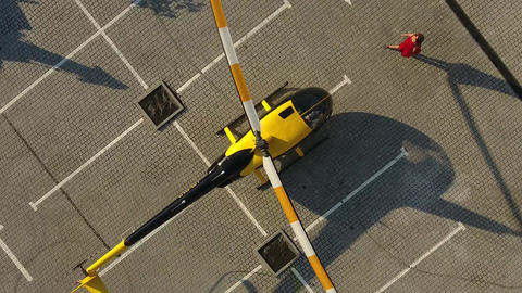 Girl in a red dress sits in a helicopter Image