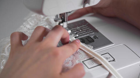 Tailor sews lingerie on a sewing machine, thread and lace, handmade underwear Footage