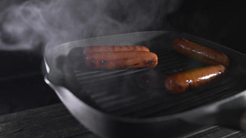 Sausages is roasting with smoke on the hot grilling pan, cooking food, meat Footage