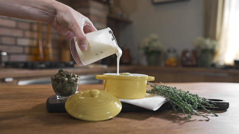 Housewife adds creme sauce to the dish, the chef spices the meal, cooking food Footage