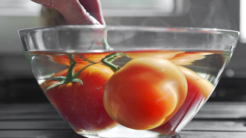 The cook blanchs tomatoes in a glass bowl with hot water, fresh vegetables Archivo