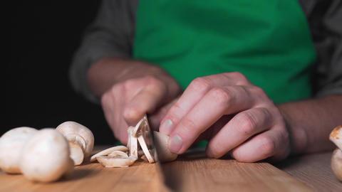 Chef shreds champignones for vegetable salad, vegetarian meal, vegan food Footage
