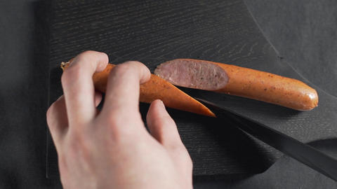 The cook cuts sausage by sharp knife on the wooden board, fas food cooking Footage