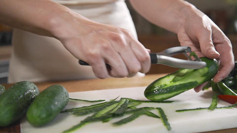 Chef peels cucumbers fof making vegetable salad with fresh greens, vegetarian Live Action
