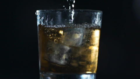 Alcohol is poured to the glass with ice cubes in slow motion, barman makes Footage