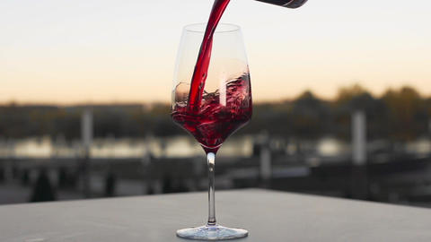 Red wine is poured to the wineglass outdoors in slow motion, bar and restaurant Footage