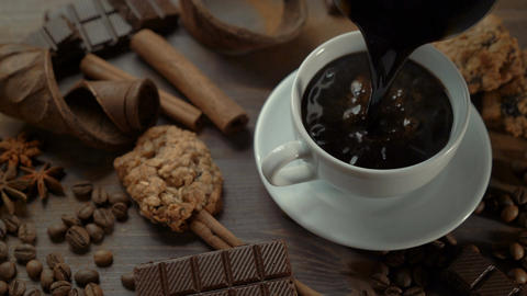Cup of hot coffee with cinnamon sticks, chocolate slices and anise star on old ビデオ