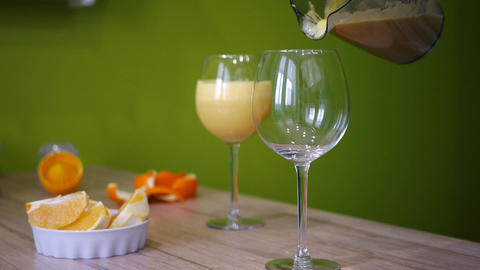Orange juice pouring in glass on color background Footage