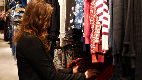 Young beautiful women shopping in fashion mall, choosing new clothes, looking Footage