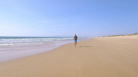 Adult Man in Shorts with a T-shirt Jogging on Ocean Beach Stock Video Footage