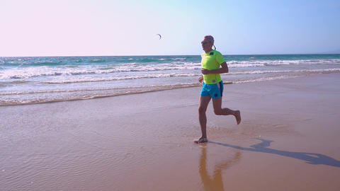 Adult Man Jogging on Ocean Beach slow motion Footage