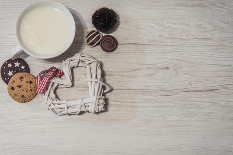 Cup of milk with sweets and a white heart Photo
