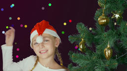 Happy young girl dancing near christmas tree in Santa red hat. Happy young Live Action