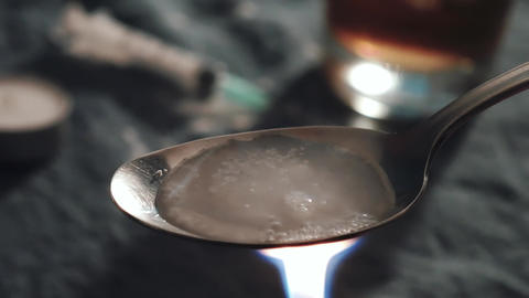 Cooking heroin on a spoon with a lighter Footage