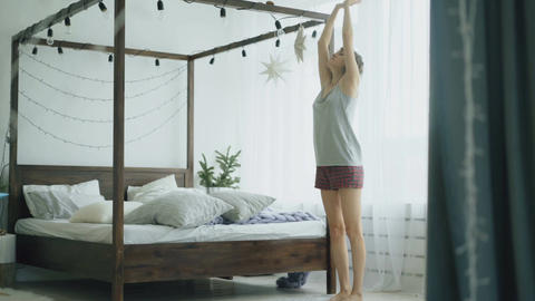 Young beautiful woman doing yoga exercise near bed in bedroom at home Footage