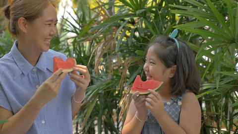 Slow motion of Asian child girl and mother eating delicious water melon Archivo