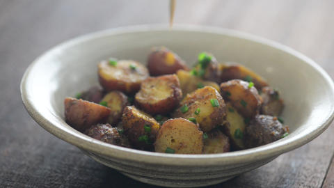 Serving tasty roasted potatoes dish Live Action