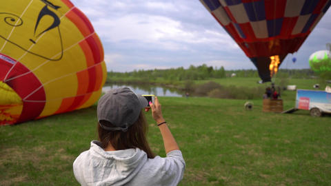 MOSCOW, RUSSIA - JUNE, 15 2017: Woman makes photo of inflating hot air balloon Footage