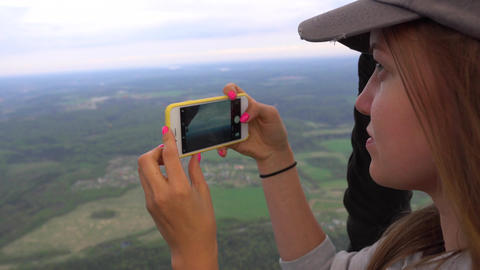 Smiling woman makes photos of hot air balloon flying above the earth. Handheld Footage