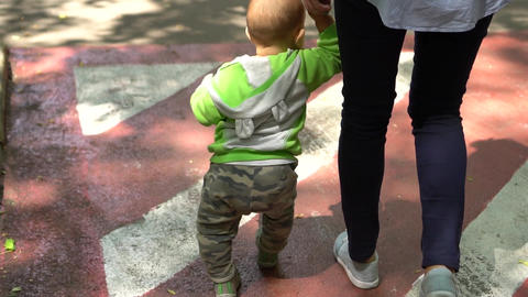 Little toddler holds on to mother's hand and walks. Handheld shot Footage