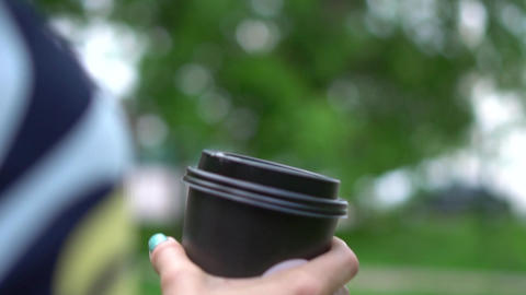 Woman holds in hand paper cup with hot beverage. Shallow depth of field Live Action