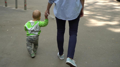 Woman walks down the street with a baby holding on to her hand Footage