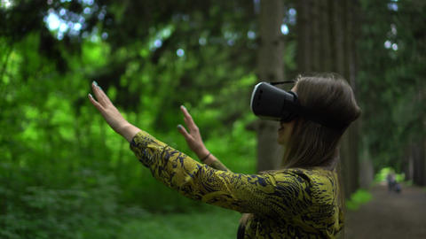 Woman in VR goggles tries to touch the objects in virtual reality. Green park as Live Action