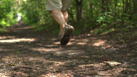 Man walks on dirty track in a green park. Close up of legs in sport sandals Footage