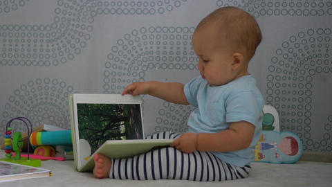 Baby boy sits and turns the pages of family photo album Footage