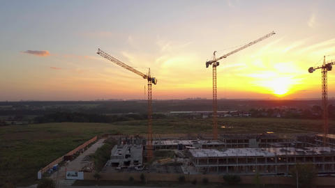 Aerial shot of construction site with building cranes against sunset sky ビデオ