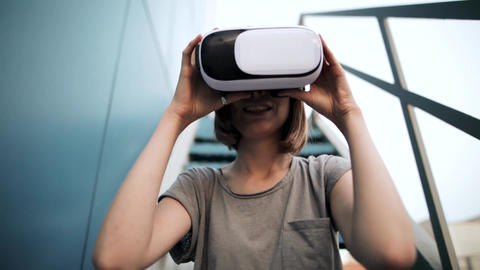 Closeup of girl with a small hands holding virtual reality glasses on a blue Archivo