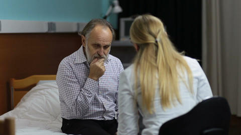 Caring doctor telling bad news to the patient Image
