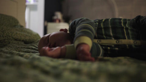 Adult covers sleeping baby with knitted plaid Footage
