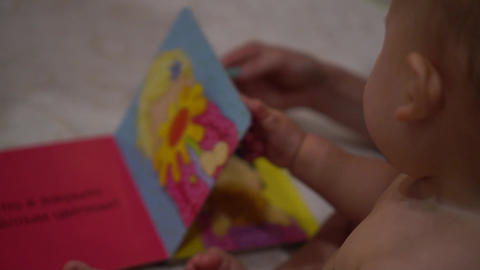 Baby turns over pages of illustrated book with bright colorful pictures ビデオ
