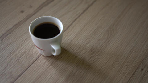 Man puts a cup of black coffe on a table. Top view Image