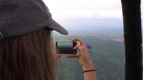 Woman makes aerial photos on a smartphone from hot air balloon busket. Handheld Footage